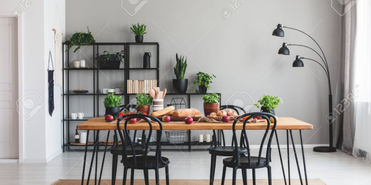 Black chairs and wooden table with food on brown carpet in grey dining room interior. Real photo
